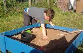 Levantó la caja de arena con tapa hecha de tablas valla tratada.