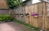 Una valla de palets con cajas de flores y abeja Hoteles