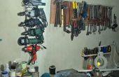 Un rack de pared simple de herramientas con el metal del patio trasero