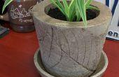 Pote de flor con adorno incrustado hoja de concreto